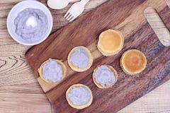 Mini pancake topped stirred taro on wood. Royalty Free Stock Images