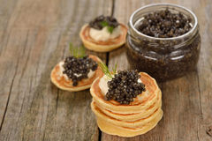 Mini pancakes with black caviar Stock Photos