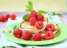 Mini pancakes with ripe fresh raspberries Royalty Free Stock Photography