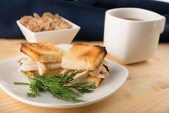 Mini panino del pane tostato del pollo con una tazza di tè e di caramello Immagini Stock Libere da Diritti