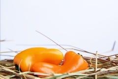 Mini paprikas amarillos con el heno en un fondo blanco fotos de archivo libres de regalías