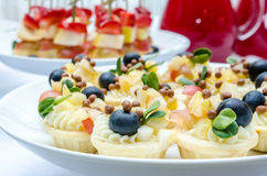 Mini party tartlets with cream cheese and fresh fruit. Set of delicious tartlets with cream, fruit and blueberries Royalty Free Stock Photos