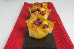 Mini pasteles de queso con los pasteles y las bayas del filo Imagen de archivo libre de regalías