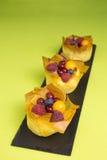 Mini pasteles de queso con los pasteles y las bayas del filo Fotos de archivo