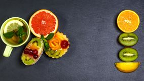 Mini pastry tartlets with fresh fruits, on serving board with kiwi, orange isolated on dark background, shale board. top view, stock photos