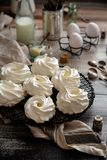 Mini pavlova branco caseiro das sobremesas da merengue no suporte de vime do metal na tabela de madeira cinzenta foto de stock