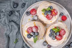 Mini pavlova cakes with fresh raspberries and blueberries royalty free stock photography