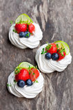 Mini  Pavlova meringue  cakes with berries and lime on rustic woo Royalty Free Stock Photo
