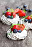 Mini  Pavlova meringue  cakes with berries and lime on rustic woo Stock Photos