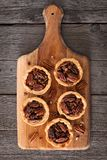 Pecan pie tarts on a wooden paddle board. Mini pecan pie tarts on a wooden paddle board against a rustic wood background stock photography
