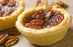 Mini Pecan Tarts. A couple of delicious mini pecan tarts and pecans on a plain background stock image