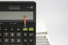 mini  people figure standing on clearing  calculator Stock Images