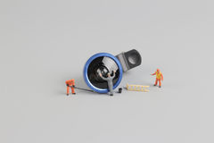 Mini people worker cleaning camera len. The mini people worker cleaning camera len Royalty Free Stock Images