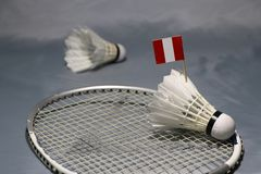 Mini Peru flag stick on the shuttlecock put on the net of badminton racket and out focus a shuttlecock. On the grey floor royalty free stock image