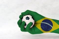 Mini piłka futbol w Brazylia fladze malował rękę na białym tle Pojęcie sport lub gra w rękojeści lub mniejszościowej sprawie fotografia royalty free