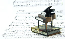 Mini piano and book song. Model of piano and book song on musicsheet Royalty Free Stock Image