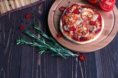 Mini pizza avec des tomates sur un fond foncé Photographie stock libre de droits