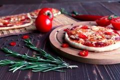 Mini pizza avec des tomates sur un fond foncé Photos libres de droits