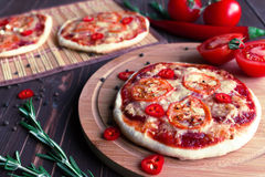 Mini pizza avec des tomates sur un fond foncé Photographie stock
