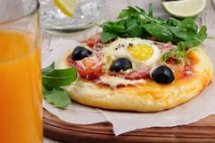 Mini pizza for breakfast. Mini pizza with sausage and egg and arugula  for breakfast Stock Photo