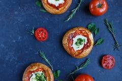 Mini Pizza casalingo con i pomodori, formaggio e bacon, lesioni e spezie su fondo scuro fotografie stock
