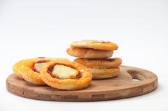 Mini pizza com queijo e salsicha em uma placa de madeira Imagem de Stock