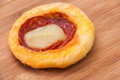 Mini pizza com salsicha em uma placa de madeira Foto de Stock