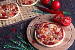 Mini pizza con los tomates en un fondo oscuro imagen de archivo
