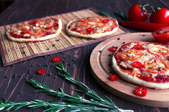 Mini pizza con los tomates en un fondo oscuro Fotos de archivo