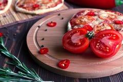 Mini pizza con los tomates en un fondo oscuro Fotos de archivo libres de regalías