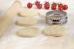 Mini pizza dough on a floury wooden board Royalty Free Stock Image