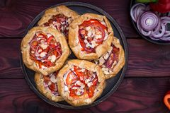 Mini pizza, galette vegetal con el queso cremoso, cebolla roja, tomates, pimienta dulce y almendras Foto de archivo