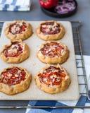 Mini- Pizza, Gemüse-galette mit Sahne Käse, rote Zwiebel, Tomaten, Gemüsepaprika und Mandeln lizenzfreie stockfotos