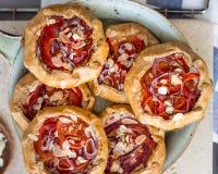 Mini- Pizza, Gemüse-galette mit Sahne Käse, rote Zwiebel, Tomaten, Gemüsepaprika und Mandeln lizenzfreies stockbild