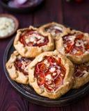 Mini- Pizza, Gemüse-galette mit Sahne Käse, rote Zwiebel, Tomaten, Gemüsepaprika und Mandeln stockfoto