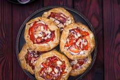 Mini- Pizza, Gemüse-galette mit Sahne Käse, rote Zwiebel, Tomaten, Gemüsepaprika und Mandeln stockbild