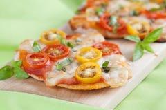 Mini- pizza med mozzarellaen, körsbärsröda tomater och basilika Fotografering för Bildbyråer