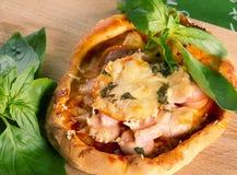 Mini- pizza med skinka, korv, tomater Arkivfoto