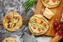 Mini- pizza med sparris Traditionell liten pizza för personlig ätapåfyllning med ost, tomater och sparris Royaltyfria Bilder