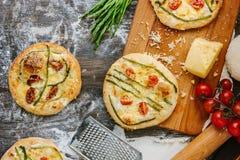 Mini- pizza med sparris Traditionell liten pizza för personlig ätapåfyllning med ost, tomater och sparris Arkivbilder