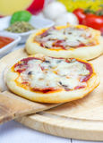 Mini pizza with salami, bacon, mushrooms and cheese Royalty Free Stock Image
