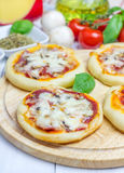 Mini pizza with salami, bacon, mushrooms and cheese. Closeup Stock Images