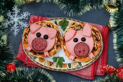 Mini pizza with sausage and cheese in the shape of a cute pigs - a symbol of 2019 royalty free stock photography