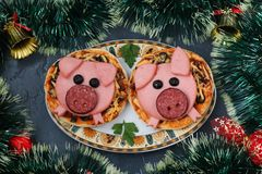 Mini pizza with sausage and cheese in the shape of a cute pigs - a symbol of 2019 stock photography