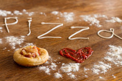 Mini pizza with sausage and cheese on wood table Royalty Free Stock Photo