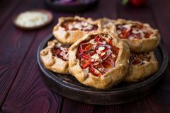 Mini pizza, vegetable galette with cream cheese, red onion, tomatoes, sweet pepper and almonds royalty free stock photography
