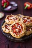 Mini pizza, vegetable galette with cream cheese, red onion, tomatoes, sweet pepper and almonds royalty free stock image