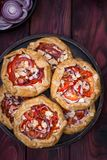 Mini pizza, vegetable galette with cream cheese, red onion, tomatoes, sweet pepper and almonds royalty free stock images