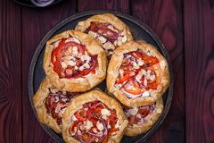 Mini pizza, vegetable galette with cream cheese, red onion, tomatoes, sweet pepper and almonds stock image