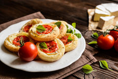 Mini pizzas with Camembert and tomato. Small pizzas with Camembert cheese, tomato and herbs Stock Photo